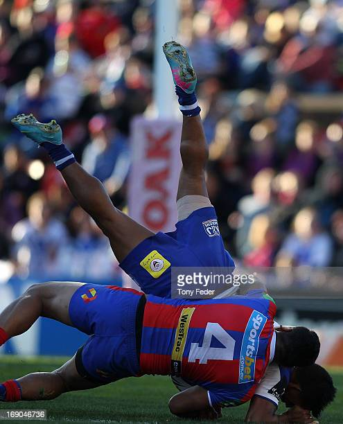 Ben Barba of the Bulldogs is tackled by Joey Leilua of the Knights during the round 10 NRL match between the Newcastle Knights and the Canterbury...