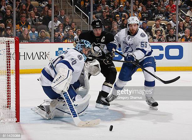 Ben Bishop makes a save in front of Sidney Crosby of the Pittsburgh Penguins and Braydon Coburn of the Tampa Bay Lightning at Consol Energy Center on...