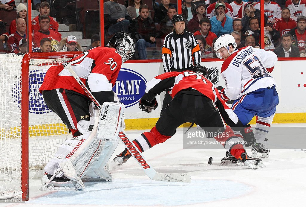 <a gi-track='captionPersonalityLinkClicked' href=/galleries/search?phrase=Ben+Bishop&family=editorial&specificpeople=700137 ng-click='$event.stopPropagation()'>Ben Bishop</a> #30 of the Ottawa Senators watches the play as team mate Sergei Gonchar #55 battles for the loose puck against <a gi-track='captionPersonalityLinkClicked' href=/galleries/search?phrase=David+Desharnais&family=editorial&specificpeople=4084305 ng-click='$event.stopPropagation()'>David Desharnais</a> #51 of the Montreal Canadiens, during an NHL game at Scotiabank Place on February 25, 2013 in Ottawa, Ontario, Canada.