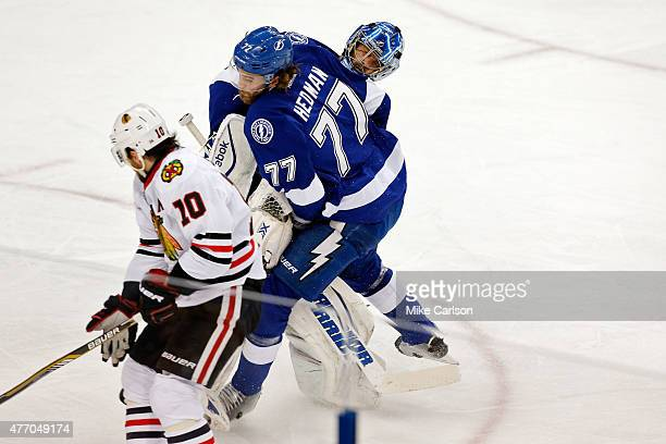 Ben Bishop of the Tampa Bay Lightning collides with Victor Hedman as Patrick Sharp of the Chicago Blackhawks skates past them with the puck on his...