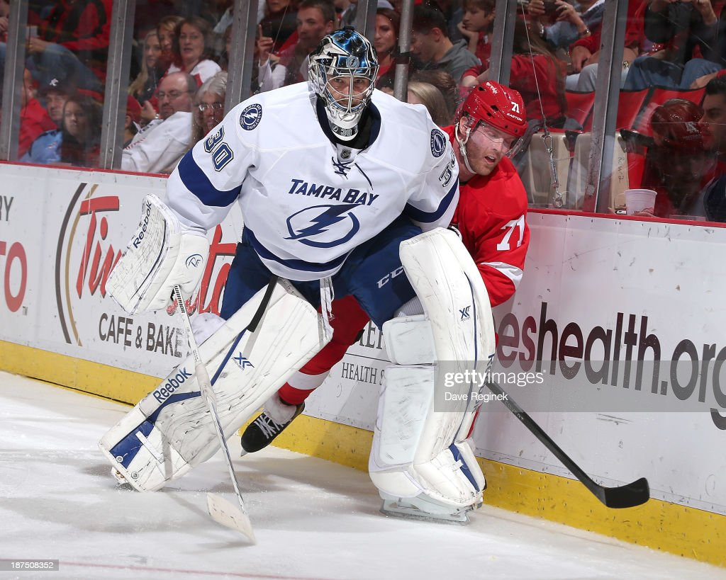 Ben Bishop #30 of the Tampa Bay Lightning interferes with Daniel Cleary #71 of the Detroit Red Wings behind the net during an NHL game at Joe Louis Arena on November 9, 2013 in Detroit, Michigan.