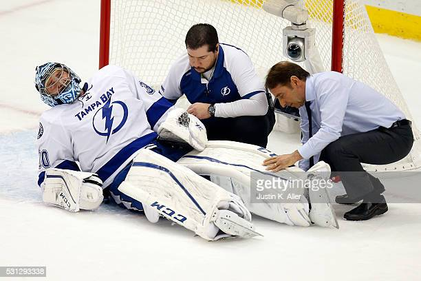 Ben Bishop of the Tampa Bay Lightning is looked over by a team physician after a play at the net during the first period against the Pittsburgh...