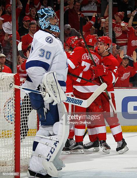 Ben Bishop of the Tampa Bay Lightning looks on as Andreas Athanasiou and Brendan Smith of the Detroit Red Wings celebrate with teammates after a...