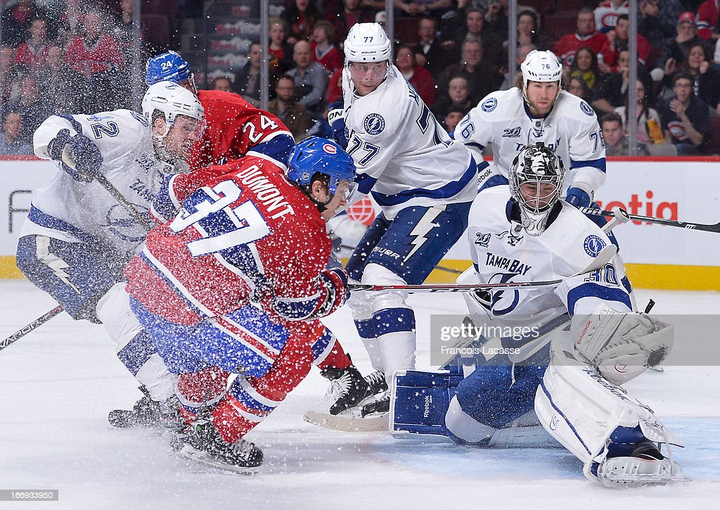 <a gi-track='captionPersonalityLinkClicked' href=/galleries/search?phrase=Ben+Bishop&family=editorial&specificpeople=700137 ng-click='$event.stopPropagation()'>Ben Bishop</a> #30 of the Tampa Bay Lightning makes a glove save as Gabriel Dumont #37 of the Montreal Canadiens looks for a rebound in NHL action on April 18, 2013 at the Bell Centre in Montreal, Quebec, Canada.