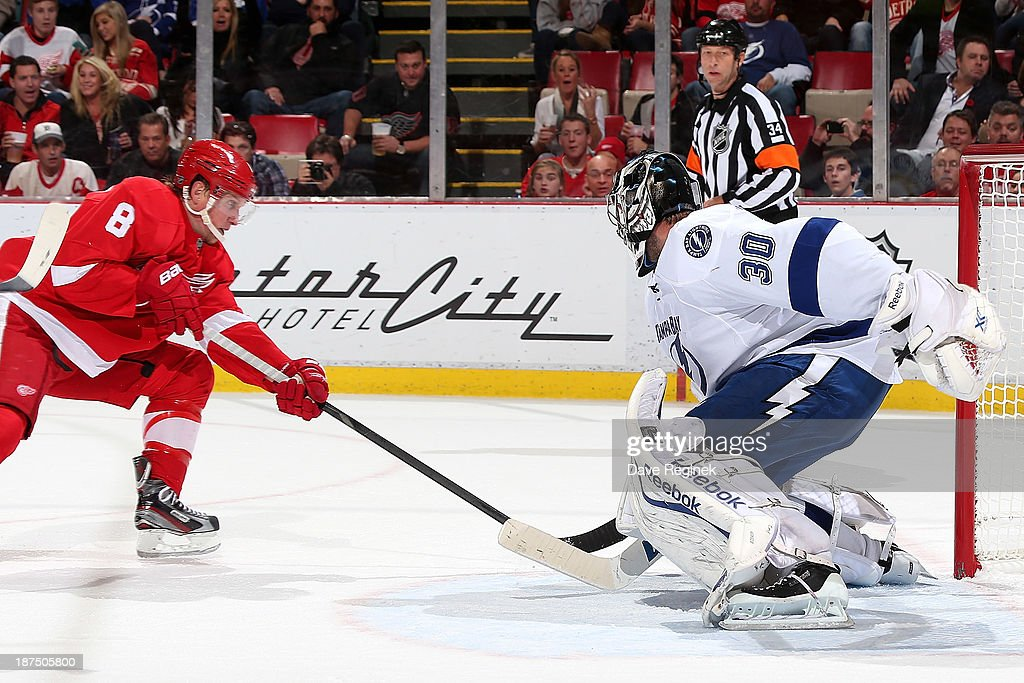 <a gi-track='captionPersonalityLinkClicked' href=/galleries/search?phrase=Ben+Bishop&family=editorial&specificpeople=700137 ng-click='$event.stopPropagation()'>Ben Bishop</a> #30 of the Tampa Bay Lightning makes a save as <a gi-track='captionPersonalityLinkClicked' href=/galleries/search?phrase=Justin+Abdelkader&family=editorial&specificpeople=2271858 ng-click='$event.stopPropagation()'>Justin Abdelkader</a> #8 of the Detroit Red Wings screens him during an NHL game at Joe Louis Arena on November 9, 2013 in Detroit, Michigan.