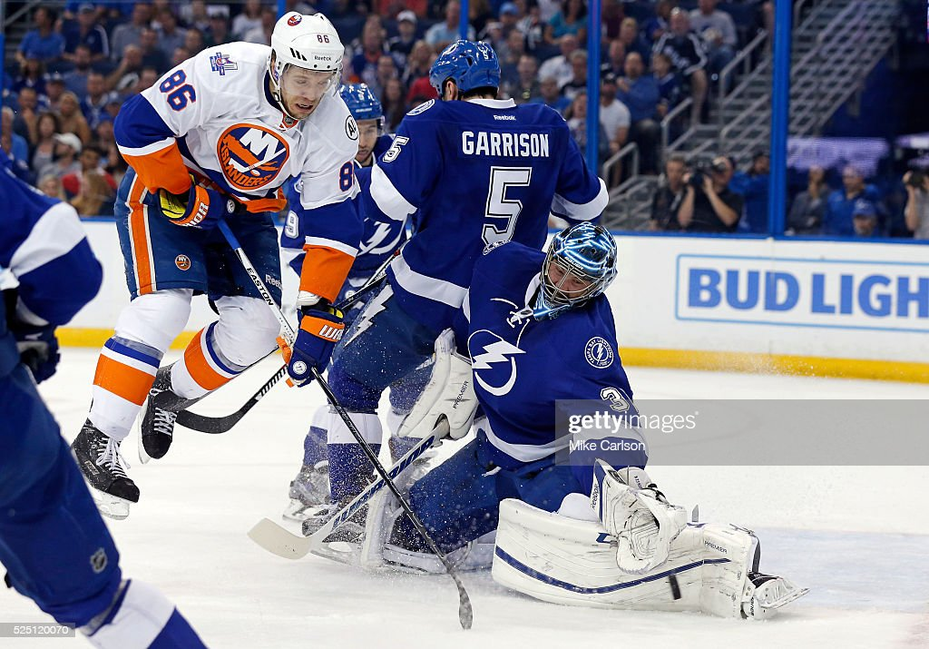 <a gi-track='captionPersonalityLinkClicked' href=/galleries/search?phrase=Ben+Bishop&family=editorial&specificpeople=700137 ng-click='$event.stopPropagation()'>Ben Bishop</a> #30 of the Tampa Bay Lightning makes a save as Nikolay Kulemin #86 of the New York Islanders crashes into <a gi-track='captionPersonalityLinkClicked' href=/galleries/search?phrase=Jason+Garrison&family=editorial&specificpeople=2143635 ng-click='$event.stopPropagation()'>Jason Garrison</a> #5 during the first period in Game One of the Eastern Conference Second Round during the 2016 NHL Stanley Cup Playoffs at Amalie Arena on April 27, 2016 in Tampa, Florida.
