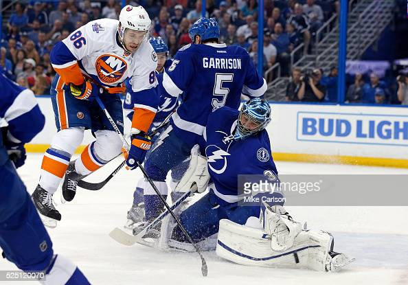 Ben Bishop of the Tampa Bay Lightning makes a save as Nikolay Kulemin of the New York Islanders crashes into Jason Garrison during the first period...