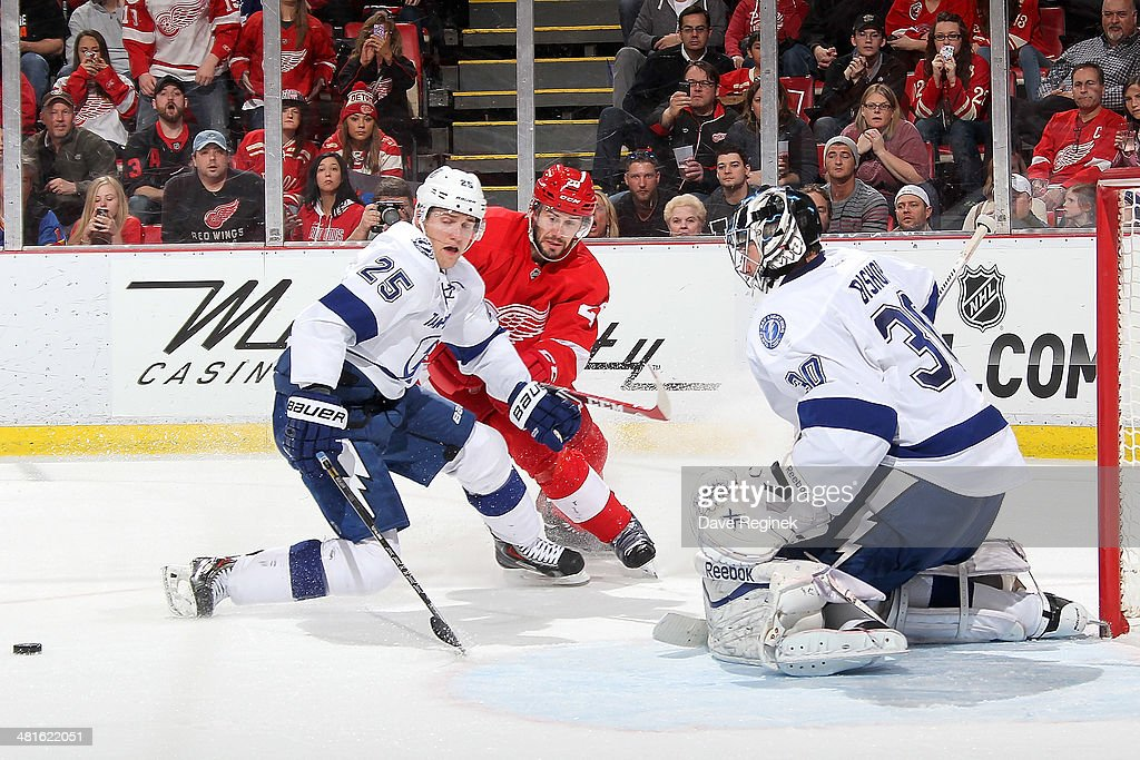 <a gi-track='captionPersonalityLinkClicked' href=/galleries/search?phrase=Ben+Bishop&family=editorial&specificpeople=700137 ng-click='$event.stopPropagation()'>Ben Bishop</a> #30 of the Tampa Bay Lightning makes a save as teammate <a gi-track='captionPersonalityLinkClicked' href=/galleries/search?phrase=Matt+Carle&family=editorial&specificpeople=582495 ng-click='$event.stopPropagation()'>Matt Carle</a> #25 tries to prevent Drew Miller #20 of the Detroit Red Wings from getting the rebound during an NHL game on March 30, 2014 at Joe Louis Arena in Detroit, Michigan.