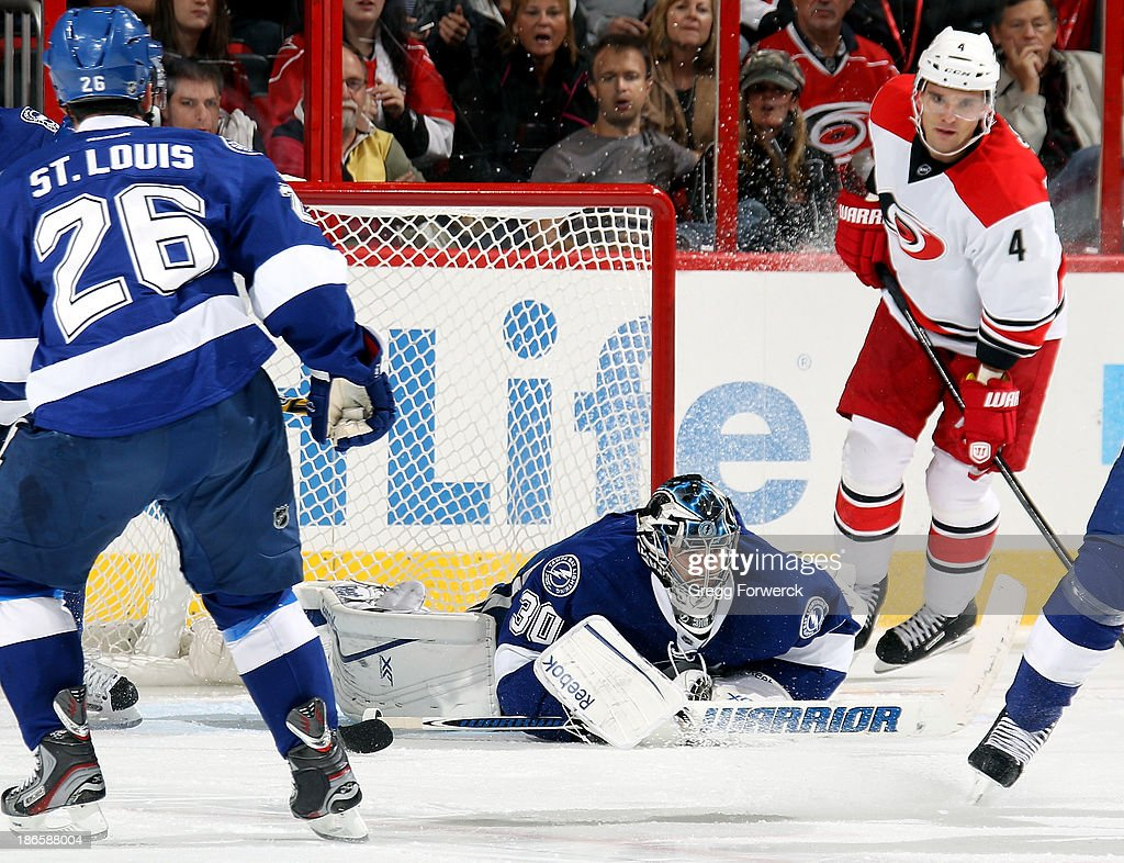 <a gi-track='captionPersonalityLinkClicked' href=/galleries/search?phrase=Ben+Bishop&family=editorial&specificpeople=700137 ng-click='$event.stopPropagation()'>Ben Bishop</a> #30 of the Tampa Bay Lightning smothers a shot as teammate Martin St Louis #26 and <a gi-track='captionPersonalityLinkClicked' href=/galleries/search?phrase=Andrej+Sekera&family=editorial&specificpeople=722503 ng-click='$event.stopPropagation()'>Andrej Sekera</a> #4 of the Carolina Hurricanes look on at PNC Arena on November 1, 2013 in Raleigh, North Carolina.