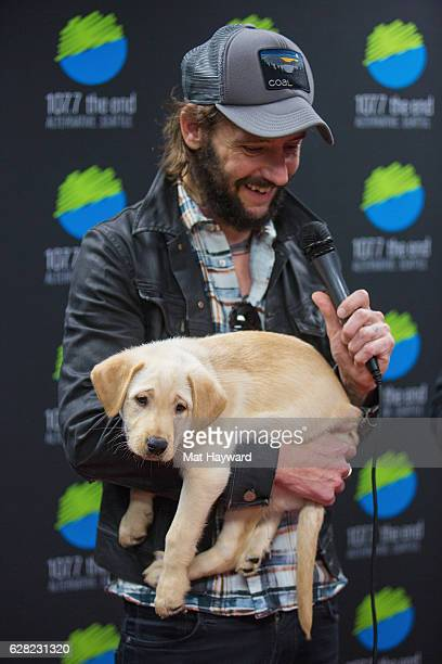 Ben Bridwell of Band Of Horses holds a Motley Zoo rescue puppy backstage during Deck The Hall Ball hosted by 1077 The End at KeyArena on December 6...