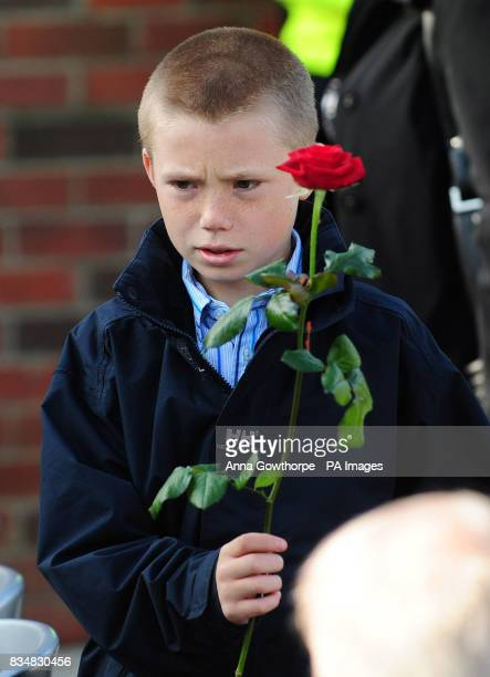 Ben Broadhurst nephew of PC Ian Broadhurst arrives at a memorial unveiling ceremony in Dib Lane in Leeds carrying a rose