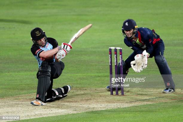 Ben Brown of Sussex Sharks sweeps the ball to the boundary as Kent Spitfires wicket keeper Sam Billings looks on during the match between Kent...