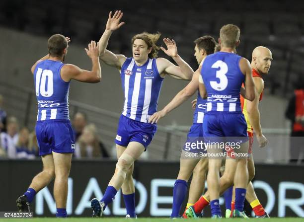 Ben Brown of the Kangaroos celebrates after kicking a goal as Gary Ablett of the Suns looks on during the round six AFL match between the North...