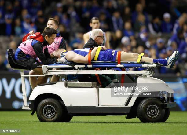 Ben Brown of the Kangaroos comes off the ground injured after being tackled by Brodie Grundy of the Magpies during the 2017 AFL round 20 match...