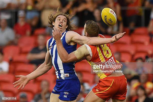 Ben Brown of the Kangaroos competes for the ball against Trent McKenzie of the Suns during the round five AFL match between the Gold Coast Suns and...