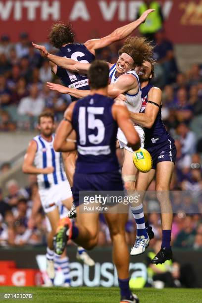 Ben Brown of the Kangaroos is sandwiched in a marking contest against David Mundy and Joel Hamling of the Dockers during the round five AFL match...