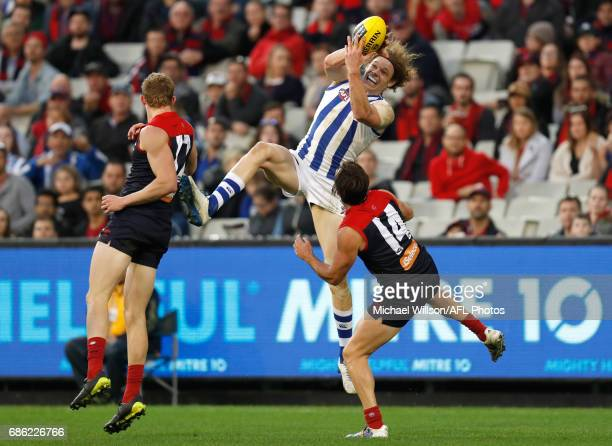 Ben Brown of the Kangaroos marks the ball over Sam Frost and Michael Hibberd of the Demons during the 2017 AFL round 09 match between the Melbourne...