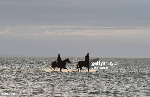 Ben Cadden riding Winx walks through the shallow waters of Altona Beach along side stable mate French Emotion with Raquel Bennett riding during a...