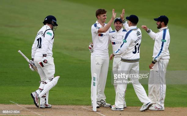 Ben Coad of Yorkshire is congratulated by team mates after taking the wicket of William Porterfield during the Specsavers County Championship One...