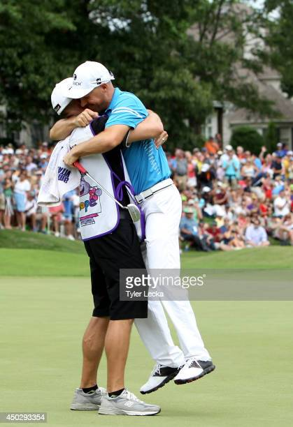 Ben Crane celebrates with caddie Joel Stock during the final round of the FedEx St Jude Classic at the TPC Southwind on June 8 2014 in Memphis...