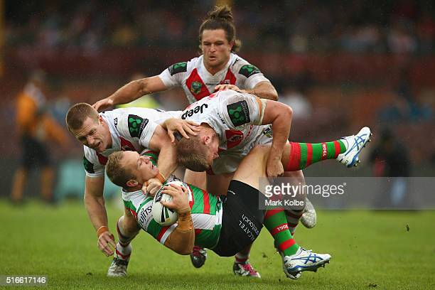 Ben Creagh and Michael Cooper of the Dragons tackle Jason Clark of the Rabbitohs during the round three NRL match between the St George Dragons and...