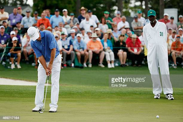 Ben Crenshaw of the United States putts on the 18th green as his caddie Justin Jackson looks on as Crenshaw played his final Masters during the...