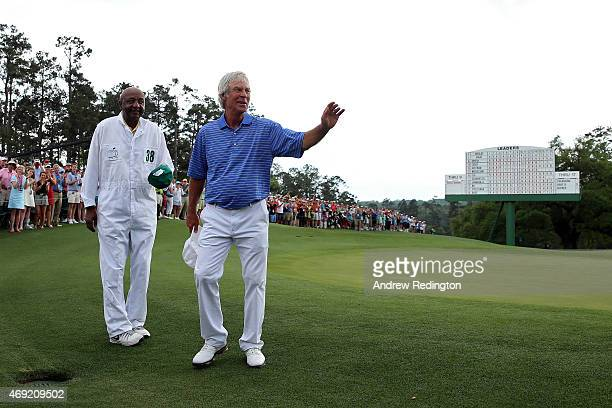 Ben Crenshaw of the United States waves to the gallery alongside caddie Carl Jackson behind the 18th green after playing his final Masters during the...