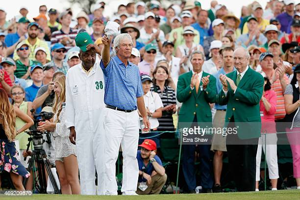 Ben Crenshaw of the United States waves to the gallery with his longtime caddie Carl Jackson behind the 18th green after playing his final Masters...