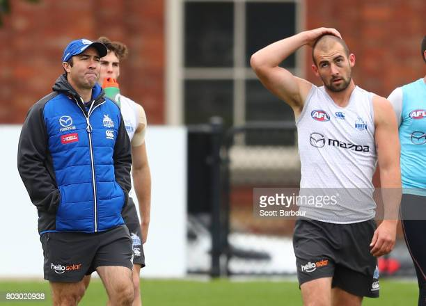 Ben Cunnington of the Kangaroos and Brad Scott coach of the Kangaroos look on during a North Melbourne Kangaroos AFL training session at Arden Street...