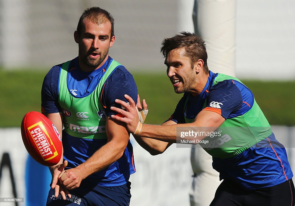 Ben Cunnington of the Kangaroos handballs away from Jamie Macmillan during a North Melbourne Kangaroos AFL media session at Arden Street Ground on May 5, 2016 in Melbourne, Australia.