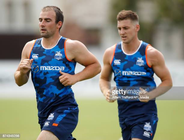 Ben Cunnington of the Kangaroos runs ahead of Shaun Atley of the Kangaroos during the North Melbourne Kangaroos training session at Arden St on...