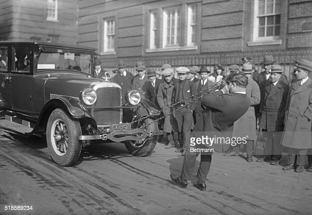 Ben Darwin of Houston Texas is shown here hauling a fully loaded limousine through the streets by means of a chain fastened to a steel comb held in...