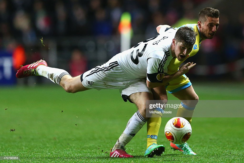 Ben Davies (L) of Swansea City is held back by <a gi-track='captionPersonalityLinkClicked' href=/galleries/search?phrase=Dries+Mertens&family=editorial&specificpeople=6524919 ng-click='$event.stopPropagation()'>Dries Mertens</a> (R) of SSC Napoli during the UEFA Europa League Round of 32 First Leg match between Swansea City and SSC Napoli at the Liberty Stadium on February 20, 2014 in Swansea, Wales.