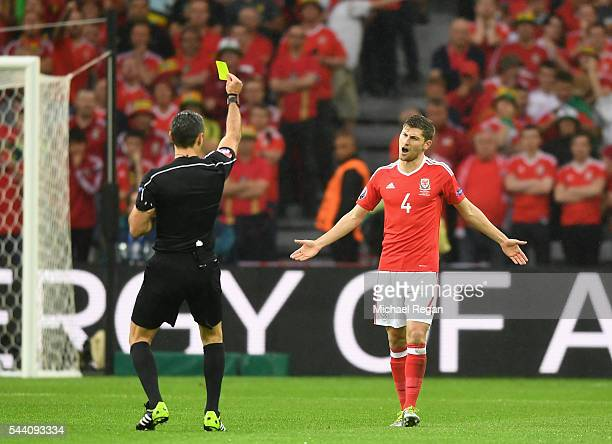 Ben Davies of Wales is shown a yellow card by referee Damir Skomina during the UEFA EURO 2016 quarter final match between Wales and Belgium at Stade...