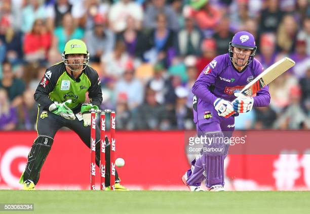 Ben Dunk of the Hurricanes bats as wicketkeeper Chris Hartley of the Thunder looks on during the Big Bash League match between the Hobart Hurricanes...