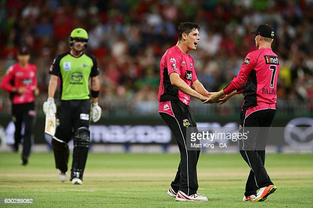 Ben Dwarshuis of the Sixers celebrates with team mates after taking the wicket of Pat Cummins of the Thunder during the Big Bash League match between...