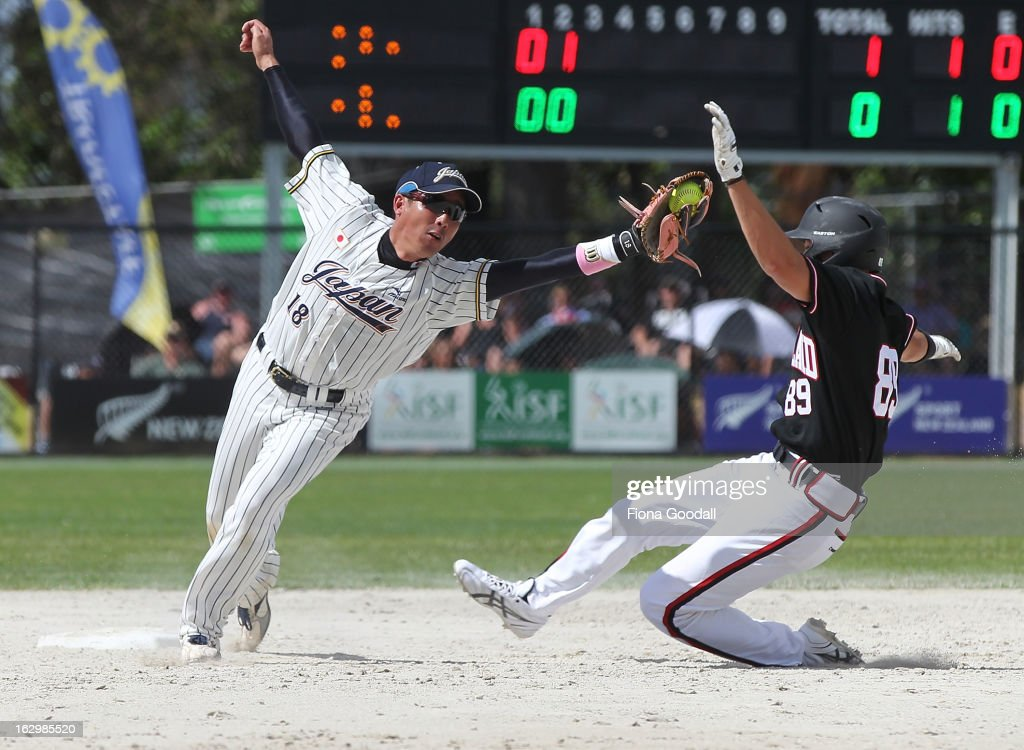Ben Enoka of New Zealand slides into second base defended by Jun Taniguchi of Japan during the pool B match between New Zealand Black Sox and Japan at Rosedale Park, Albany on March 3, 2013 in Auckland, New Zealand.