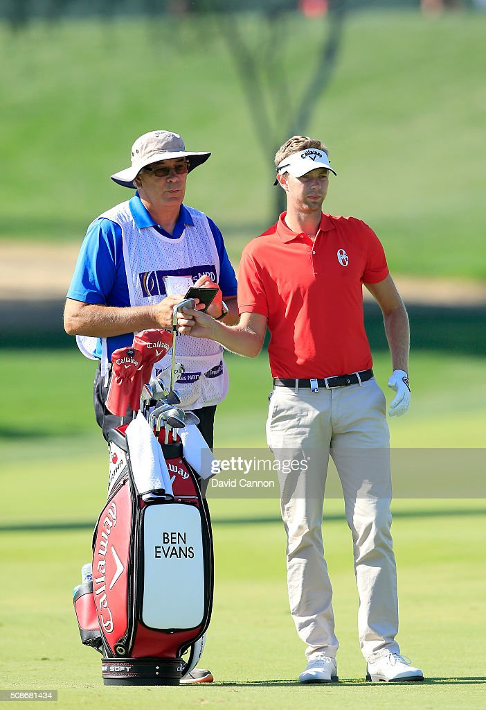 Ben Evans of England chooses his club for his second shot at the par 4, first hole with his father Glyn Evans as his caddie during the third round of the 2016 Omega Dubai Desert Classic on the Majlis Course at the Emirates Golf Club on February 6, 2016 in Dubai, United Arab Emirates.