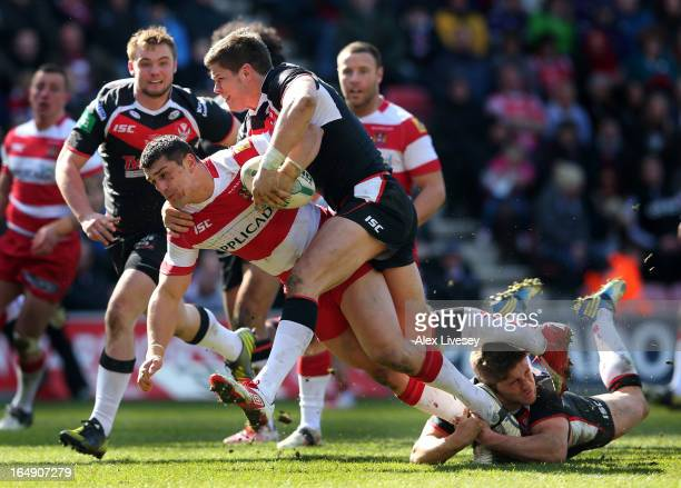 Ben Flower of Wigan Warriors is tackled by Louie McCarthyScarsbrook and Tom Makinson of St Helens during the Super League match between Wigan...