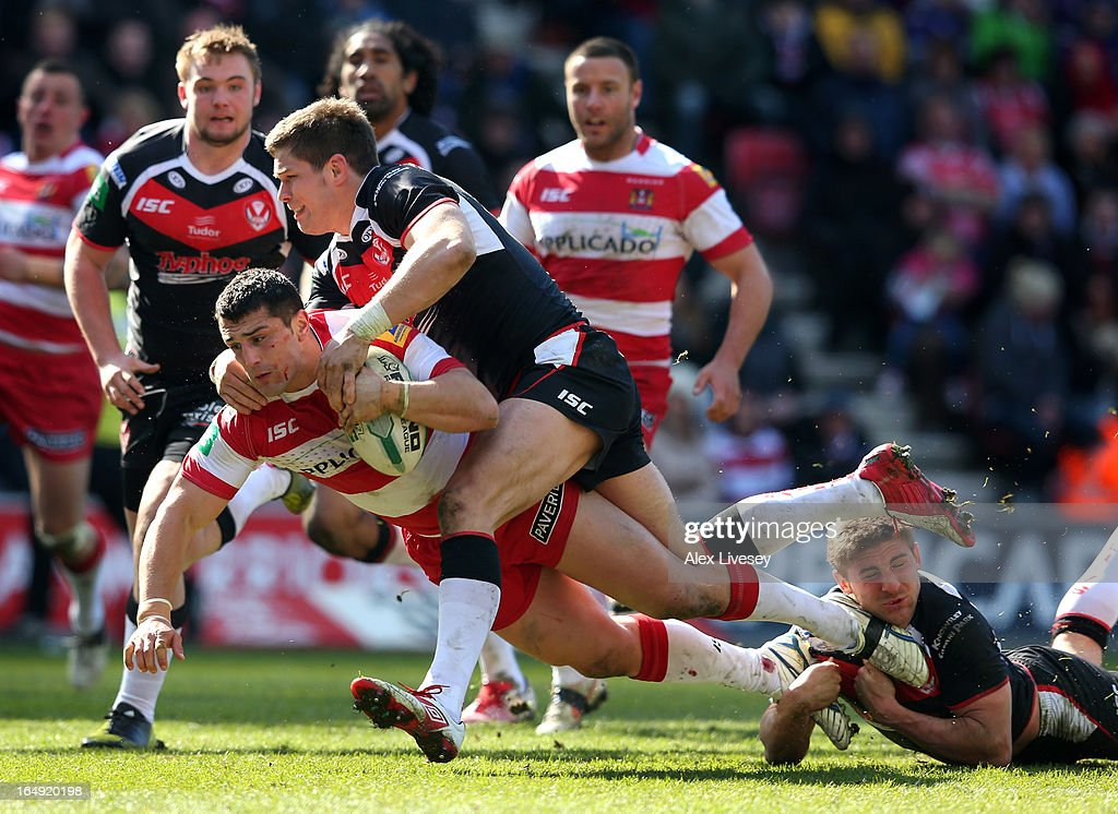 Ben Flower of Wigan Warriors is tackled by Louie McCarthy-Scarsbrook and Tom Makinson of St Helens during the Super League match between Wigan Warriors and St Helens at DW Stadium on March 29, 2013 in Wigan, England.