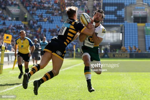 Ben Foden of Northampton challenges Josh Bassett to the ball during the Aviva Premiership match between Wasps and Northampton Saints at The Ricoh...