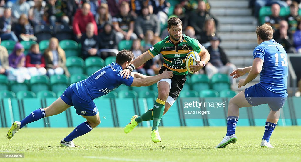 Ben Foden of Northampton is held by Sam Coglan-Murray during the pre season friendly match between Northampton Saints and Leinster at Franklin's Gardens on August 23, 2014 in Northampton, England.