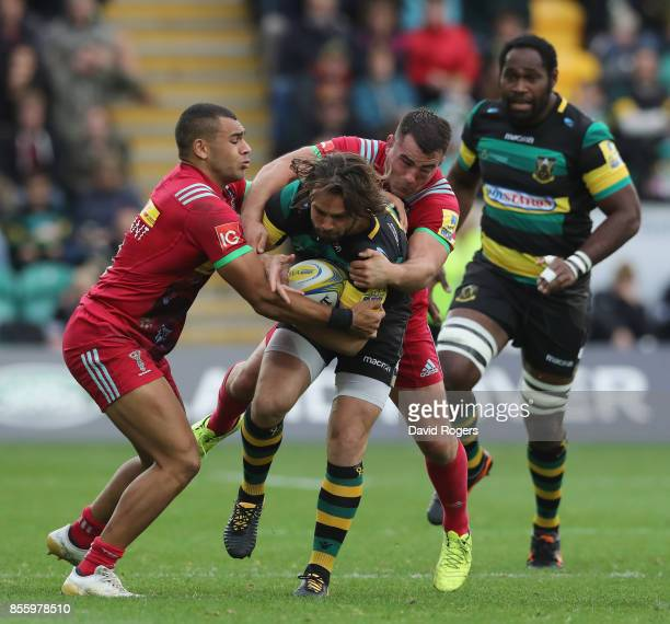 Ben Foden of Northampton is tackled by Dave Ward and Joe Marchant during the Aviva Premiership match between Northampton Saints and Harlequins at...