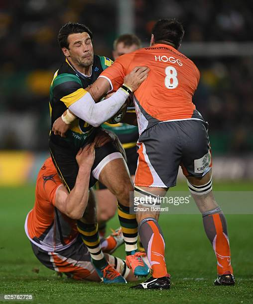 Ben Foden of Northampton Saints is tackled by Callum Chick and Ally Hogg of Newcastle Falcons during the Aviva Premiership match between Northampton...
