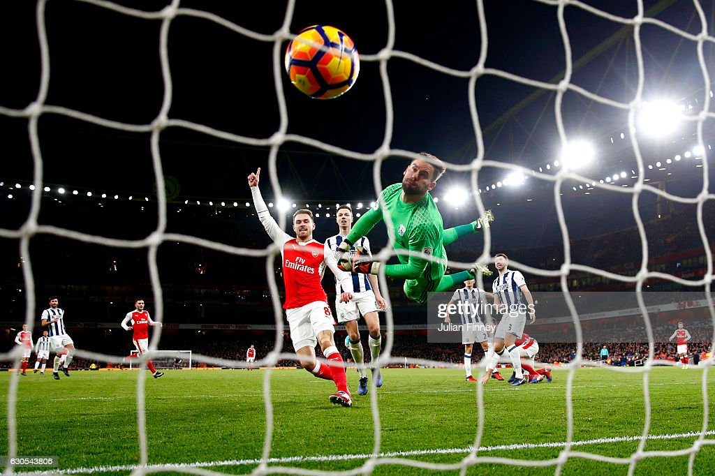 Ben Foster of West Bromwich Albion dives in vain as Olivier Giroud of Arsenal scores the opening goal during the Premier League match between Arsenal and West Bromwich Albion at Emirates Stadium on December 26, 2016 in London, England.