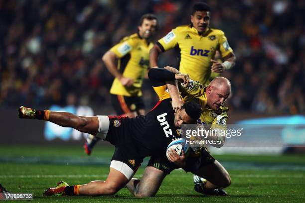 Ben Franks of the Hurricanes tackles Lelia Masaga of the Chiefs during the round 18 Super Rugby match between the Chiefs and the Hurricanes at...