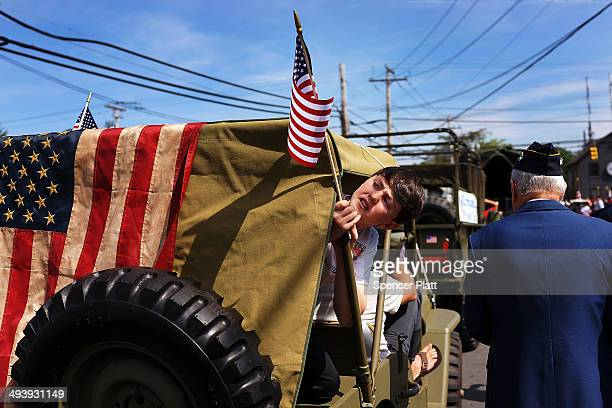 Ben Funk sticks his head out while securing an American Flag to a vintage jeep in the annual Memorial Day Parade on May 26 2014 in Fairfield...