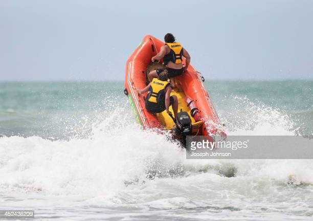 Ben Funnell of the Crusaders team rides in a surfboat with a surf lifesaver during a surf lifesaving training day on November 29 2013 in Christchurch...