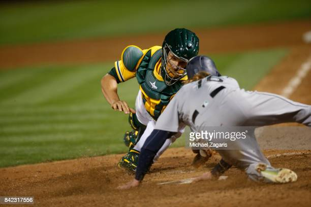Ben Gamel of the Seattle Mariners avoids the tag at home by Dustin Garneau of the Oakland Athletics during the game at the Oakland Alameda Coliseum...