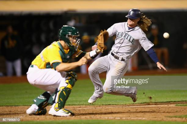 Ben Gamel of the Seattle Mariners slides past Dustin Garneau of the Oakland Athletics to score in the eighth inning at Oakland Alameda Coliseum on...